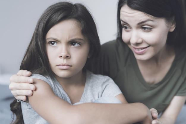 Moeder omarmt onverschillig meisje en glimlach