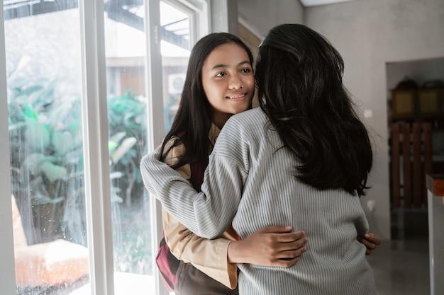 Moeder omhelst dochter voordat ze naar school gaat