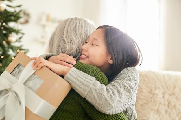 Moeder omhelst haar dochtertje en feliciteert haar thuis met eerste kerstdag