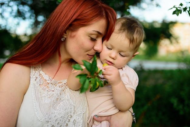 Moeder omhelst haar eenjarige dochter in het park.