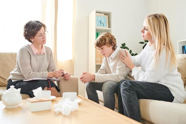 Moeder ondersteunende zoon bij therapiesessie