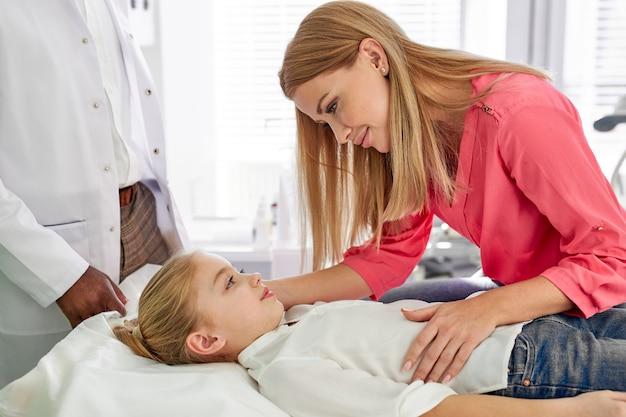 Moeder ondersteunt kind meisje lijdt aan een ziekte, schattige ouders hebben praten met haar dochter liggend op bed. in het ziekenhuis