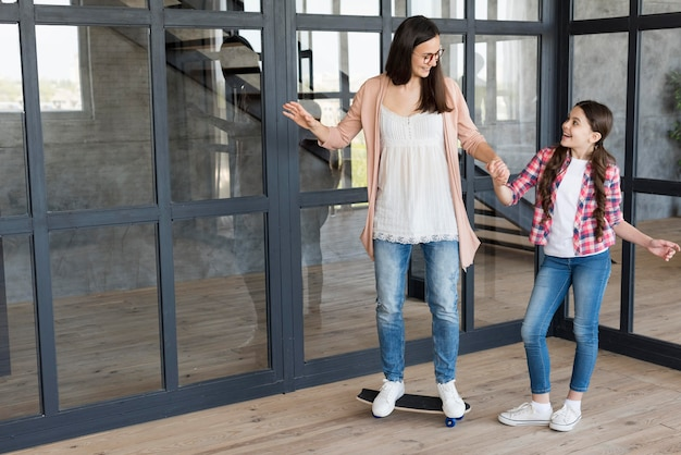 Moeder onderwijs meisje om skateboard te rijden