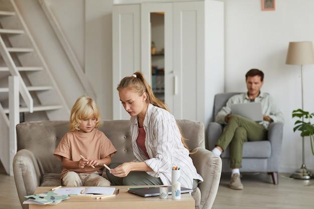 Moeder onderwijst haar zoon aan de tafel in de kamer met vader die op laptop werkt