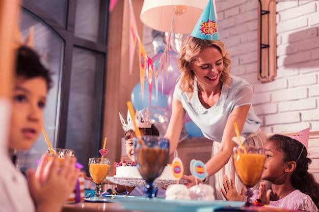 Moeder op feestje. vriendelijke liefhebbende moeder die gelukkig glimlacht en zich gelukkig voelt terwijl ze de verjaardagstaart op de feesttafel zet
