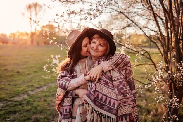 Moeder op middelbare leeftijd en haar volwassen dochter die in bloeiende tuin koesteren. moederdag concept. familiewaarden
