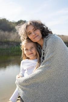 Moeder poseert met haar jonge dochter buitenshuis