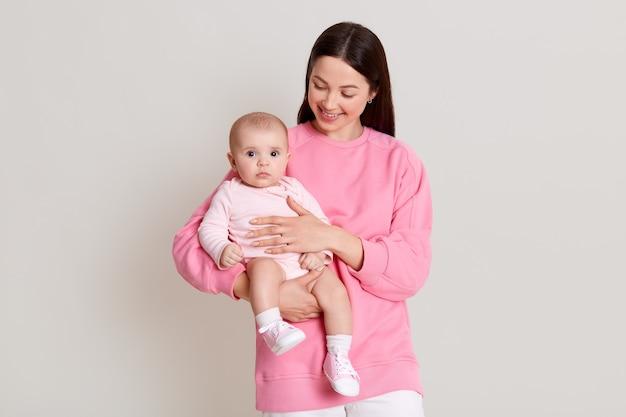 Moeder poseren met babymeisje, gelukkige familie plezier indoor, vrolijke lieve jongen met mama, moeder en kind, gezonde peuter, vrouw met donker haar dragen casual kleding kijken naar haar dochter.