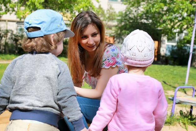 Moeder praat met de tweeling van de kinderen en vertelt hen hoe ze moeten handelen