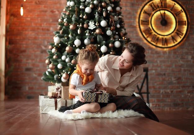 Moeder praat met haar dochtertje, die bij de kerstboom zit.