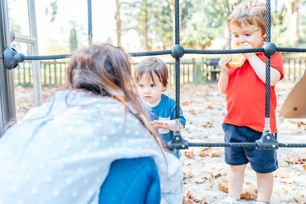 Moeder praat met haar een- en driejarige zoon over de gedragsregels in het park. onderwijs concept