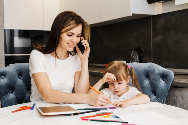Moeder praten aan de telefoon en haar dochter helpen
