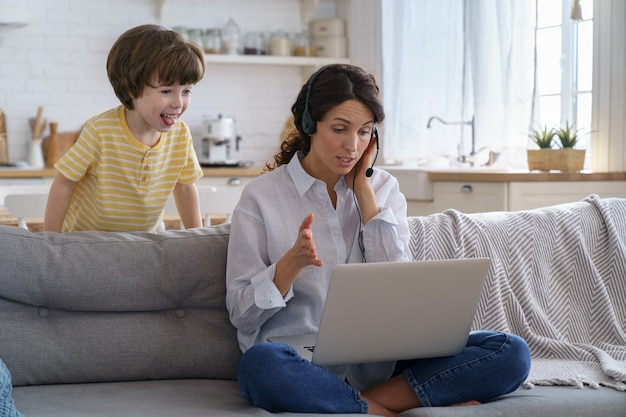 Moeder praten over videogesprek extern werk op laptop vanuit huis met jonge kinderen maken lawaai toont tong