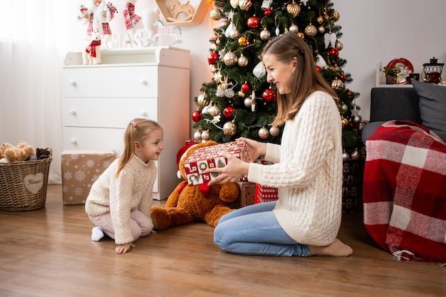 Moeder presenteert geschenkdozen aan haar kleine meisje