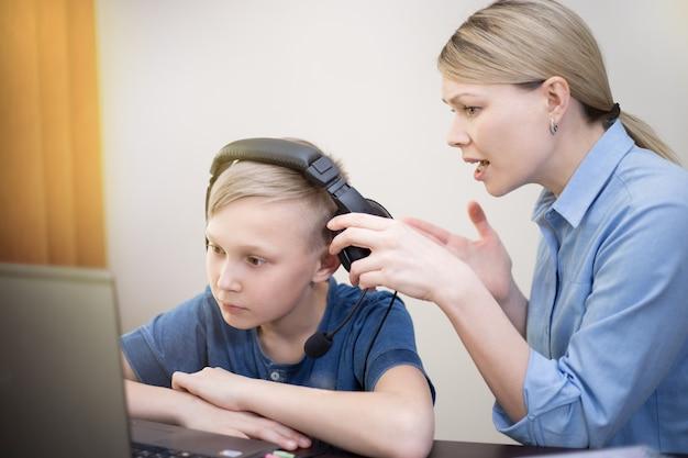 Moeder probeert de aandacht te trekken van de zoon die met een notitieboekje en koptelefoon werkt