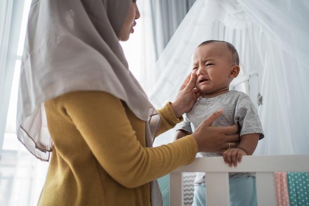 Moeder probeert haar huilende kind te troosten bij de wieg