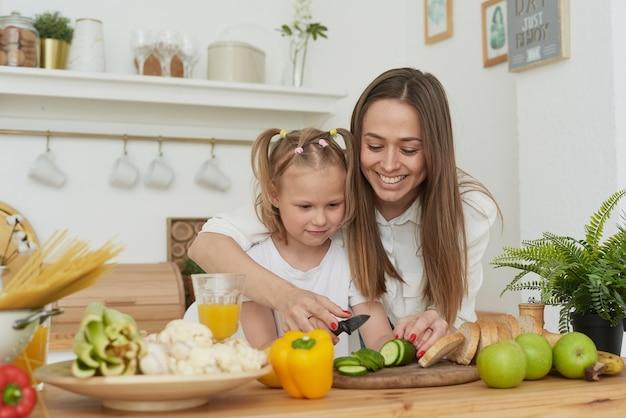 Moeder regelt het snijden van groenten van haar dochter. kook opleiding.