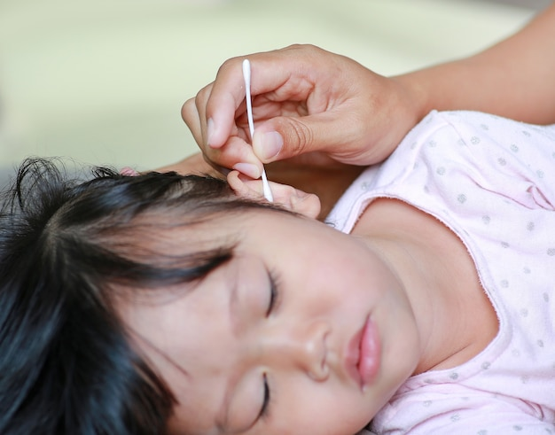Moeder reiniging baby oor met wattenstaafje.