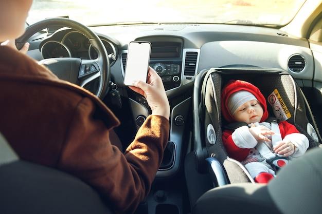 Moeder rijdt in de auto met de telefoon in haar handen, terwijl haar kleine kind voorin zit met een autostoeltje vastgemaakt met een veiligheidsgordel.