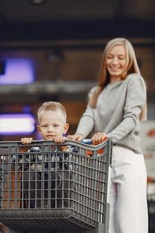 Moeder rijdt in een karretje. familie op een parkeerplaats bij een supermarkt.
