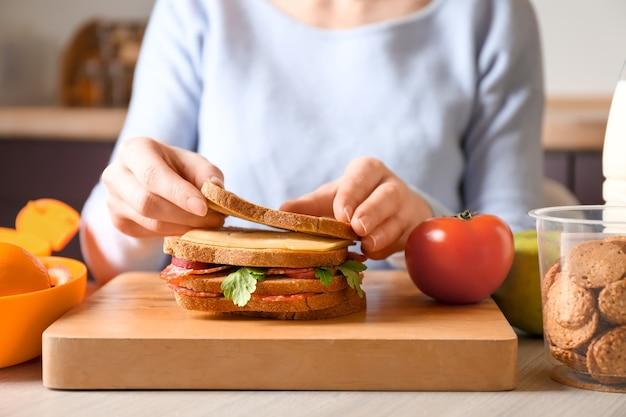Moeder sandwich voorbereiden op schoollunch op tafel