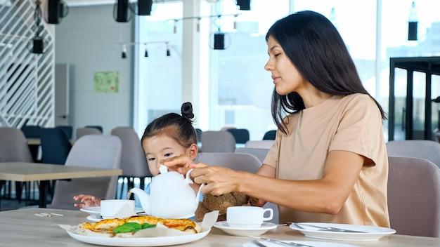 Moeder schenkt thee uit theepot in kopje zittend bij meisje en pizza