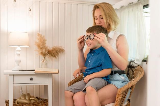 Moeder schikt de bril van haar zoon