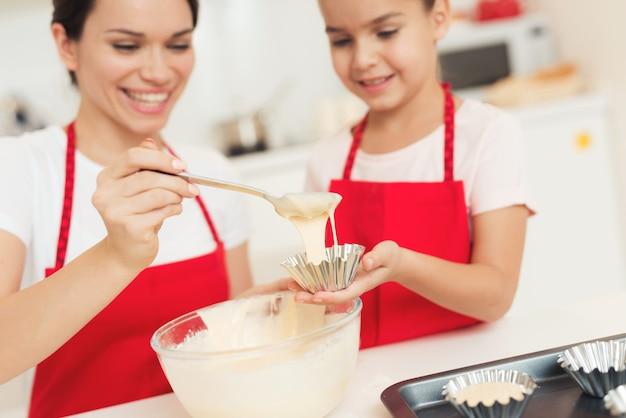 Moeder schikt het deeg in de koekjessnijder.