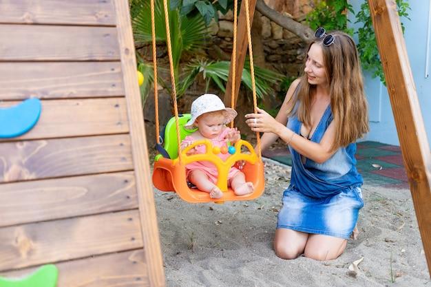 Moeder schommelt een meisje op een schommel op de speelplaats in de zomer in de tuin van het huis