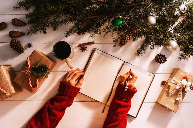 Moeder schrijft naar notitieboek en takenlijst met cadeaus voor kerstmis en nieuwjaar