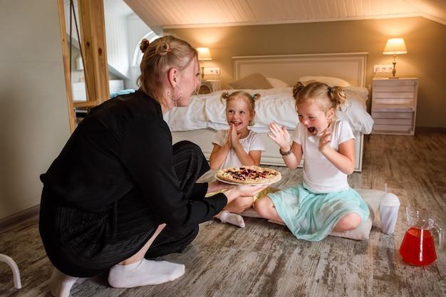 Moeder serveert pizza aan dochters, kinderen zijn blij en klappen in hun handen.