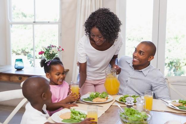 Moeder serveert sap aan haar familie tijdens de lunch