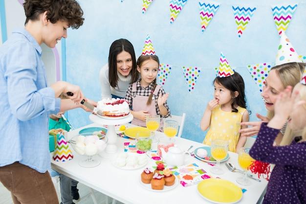 Moeder snijden taart met mes voor kinderen