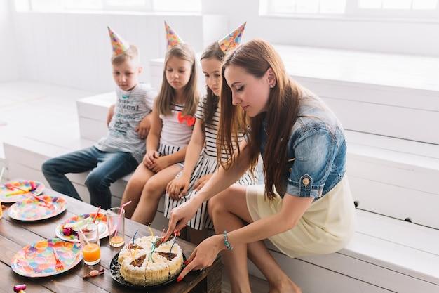 Moeder snijden verjaardagstaart voor kinderen