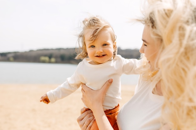 Moeder speelt buiten met haar kleine kind op een strand en houdt haar in de armen