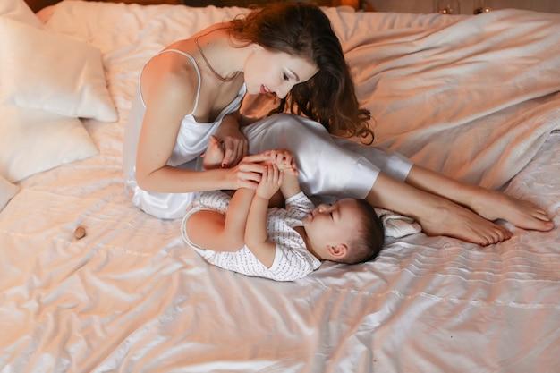 Moeder speelt en heeft plezier op het bed met haar zoontje