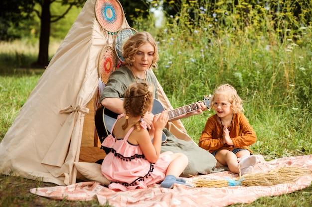 Moeder speelt gitaar voor haar kinderen, kleine dochters. multicultureel festival of kinderfeestje. familie zit naast wigwam of tipi-decoratie. boho-stijl decoraties.