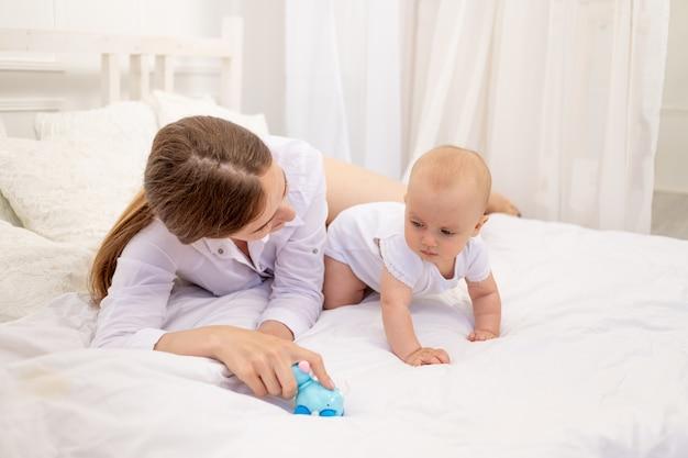 Moeder speelt met baby 6 maanden liggend op een wit bed, vrije tijd moeder met baby
