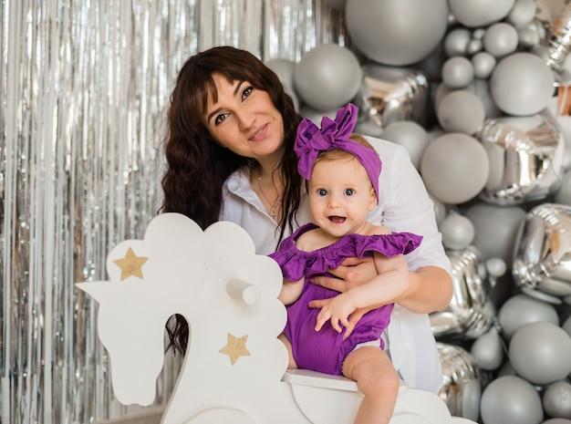 Moeder speelt met baby dochter zittend op een wit paard op een grijze folie achtergrond met ballonnen