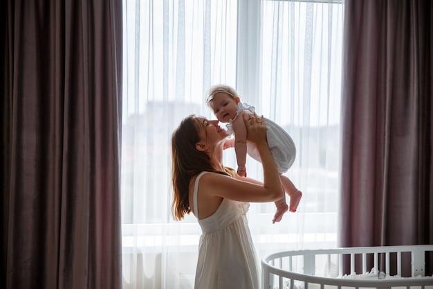 Moeder speelt met baby in slaapkamer, gaat omhoog