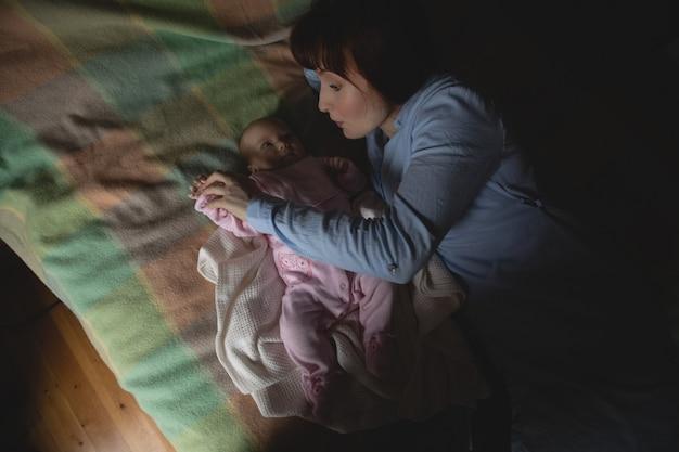 Moeder speelt met haar baby in de slaapkamer