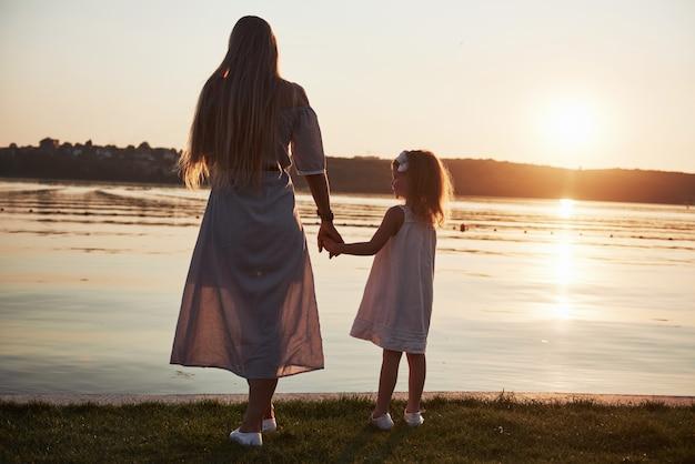 Moeder speelt met haar baby op vakantie in de buurt van de oceaan, silhouetten bij zonsondergang
