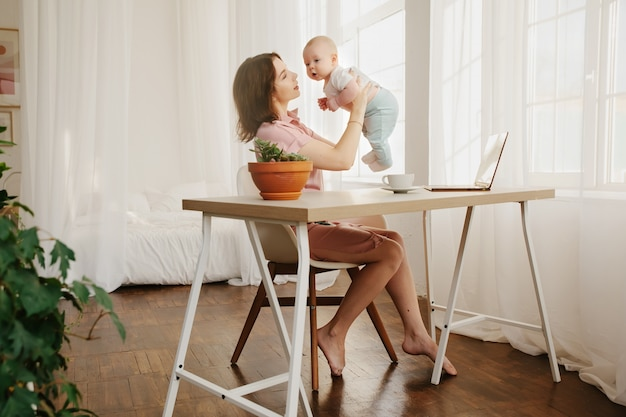 Moeder speelt met haar baby. thuiskantoor, freelance
