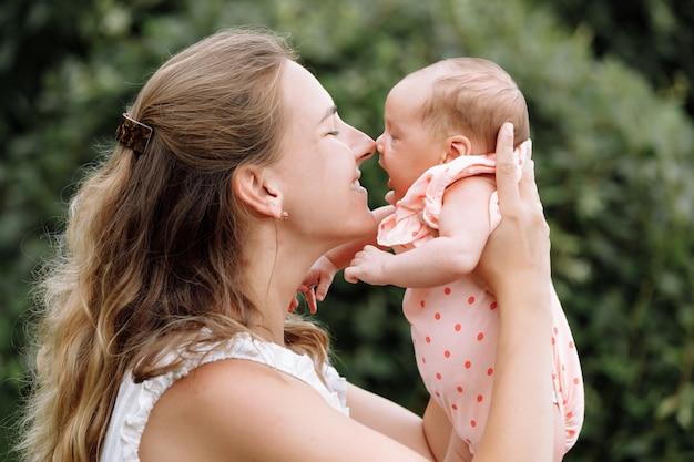 Moeder speelt met haar babymeisje buiten op zomerdag