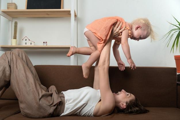 Moeder speelt met haar dochter en heft haar boven haar op. plezier in huis.