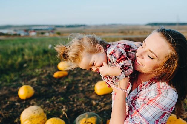 Moeder speelt met haar dochter op een veld met pompoenen
