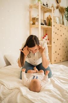 Moeder speelt met haar dochter op een witte deken op het bed in de kamer