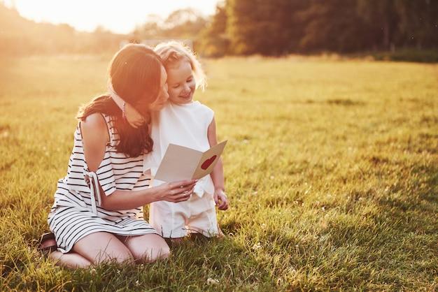 Moeder speelt met haar dochter op straat in het park bij zonsondergang