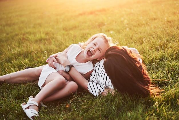 Moeder speelt met haar dochter op straat in het park bij zonsondergang.