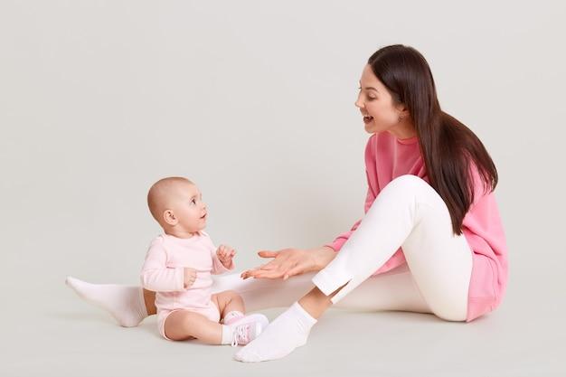 Moeder speelt met haar dochter wit samen zittend op de vloer, kind draagt bodysuit en sokken, mama palm geven aan haar baby en lachen, poseren geïsoleerd over witte muur.